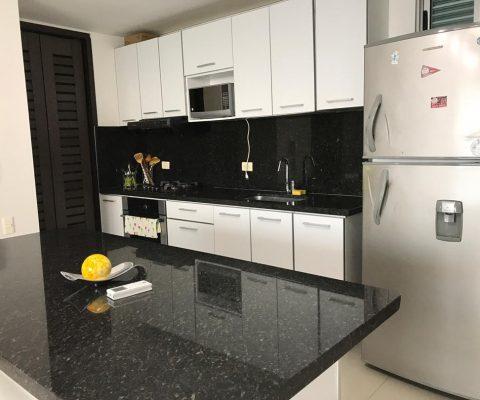 cocina abierta con nevera y comedor tipo isla en granito negro