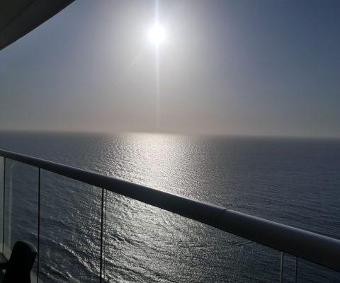 desde un balcón se ve el sol de la tarde brillar fuerte sobre un mar en calma hasta el horizonte