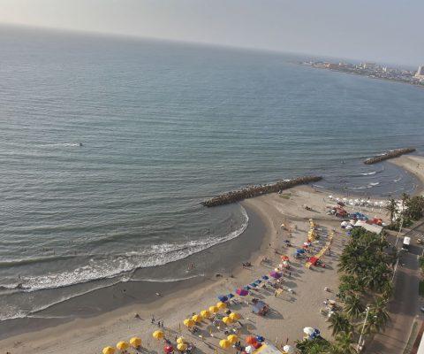 desde un balcón se ve la playa turística de Bocagrande en Cartagena con muchas sombrillas playeras típicas del lugar