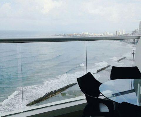balcon con vista al mar de cartagena y mesa en vidrio con sillas en plastico color cafe oscuro