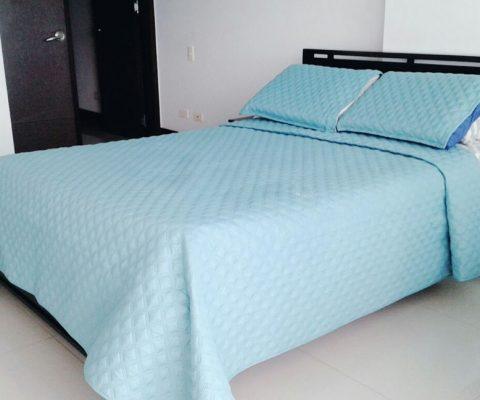 habitacion con cama doble y mesa de noche en madera color cafe oscuro y cubrecama color azul