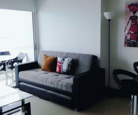 sofa cama en cuero color negro con gris, mesa de centro en vidrio, y lampara alta con paredes color blanco