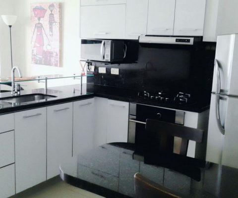 cocina color blanca con mesones color oscuro, horno, microondas y nevera color gris