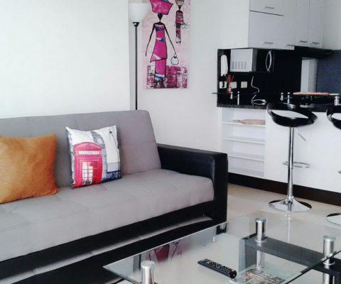 sala con sofacama color gris y negro mesa de centro en vidrio y cocina enchapada color blanco con meson en granito oscuro