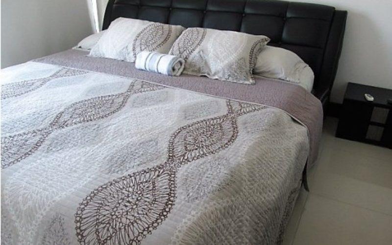 habitacion con cama doble y mesa de noche color negro, paredes blancas y blackout