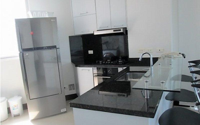 cocina integral color blanco con meson en granito negro, barra americana y nevera