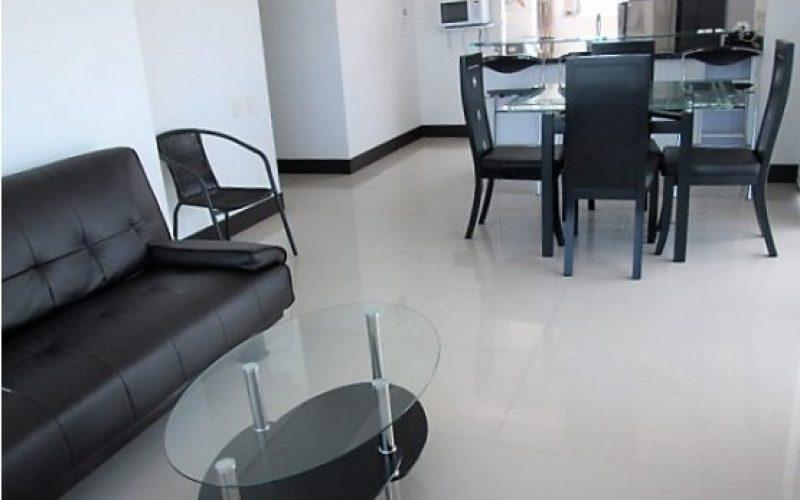 sofa en cuero color negro y comedor de cuatro puestos en madera color oscuro con mesa en vidrio y paredes blancas