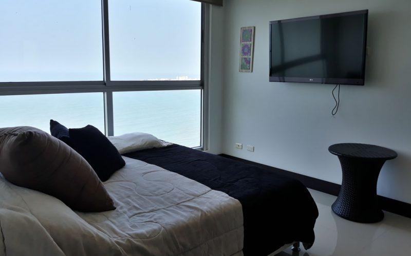 habitación con cama doble, mesa auxiliar y tv, el ventanal piso a techo da vista sobre el mar de Cartagena