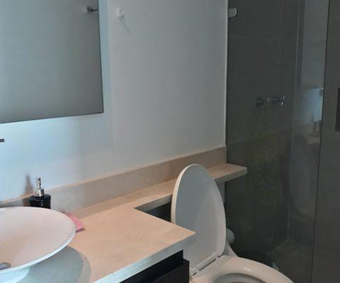baño con lavamanos de sobreponer en porcelana y grifería moderna junto a encimera de piedra y ducha con divisiones en vidrio