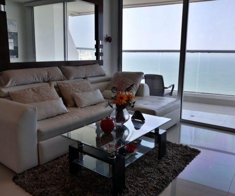 sala de estar con sofá de cuero blanco en L y mesa de café, un ventanal da salida a un balcón con vista al mar