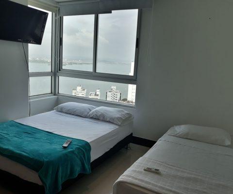 habitación con vista a la bahía de Cartagena, está equipada con una cama sencilla, una cama doble y un tv de pared