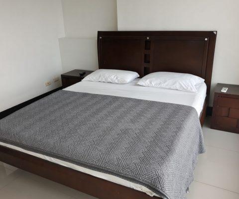 cama doble y dos nocheros de estilo tradicional dentro de una habitación con pisos en porcelanato