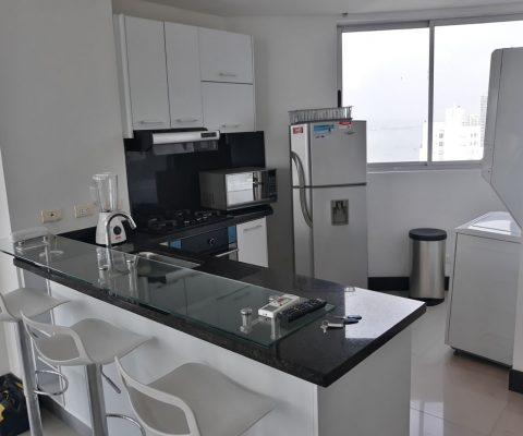 cocina abierta en colores blanco y negro barra en vidrio y butacas para 3 personas. una ventana da vista a bahía de Cartagena