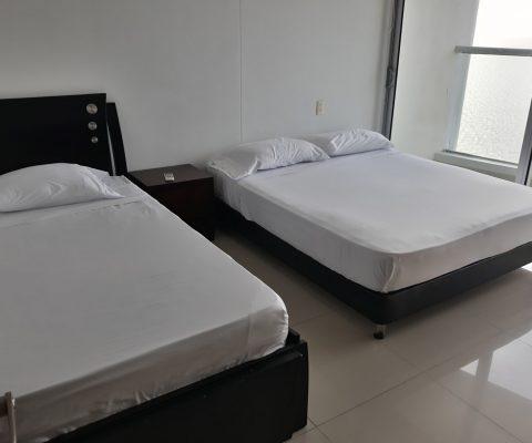 habitación con 2 camas dobles y un nochero, a través de la ventana piso a techo se ve un balcón que tiene vista al mar