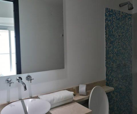 baño con lavamanos de sobreponer en porcelana, encimera de piedra, sanitario tradicional y ducha con detalle de enchape azul