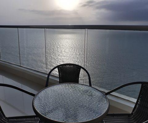 desde un balcón amoblado con 4 sillas metálicas y una mesa redonda se puede ver un mar en calma