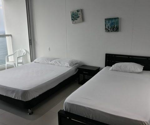 habitación equipada con 2 camas una doble, una sencilla y un nochero, una puerta ventana sale al balcón con vista al mar