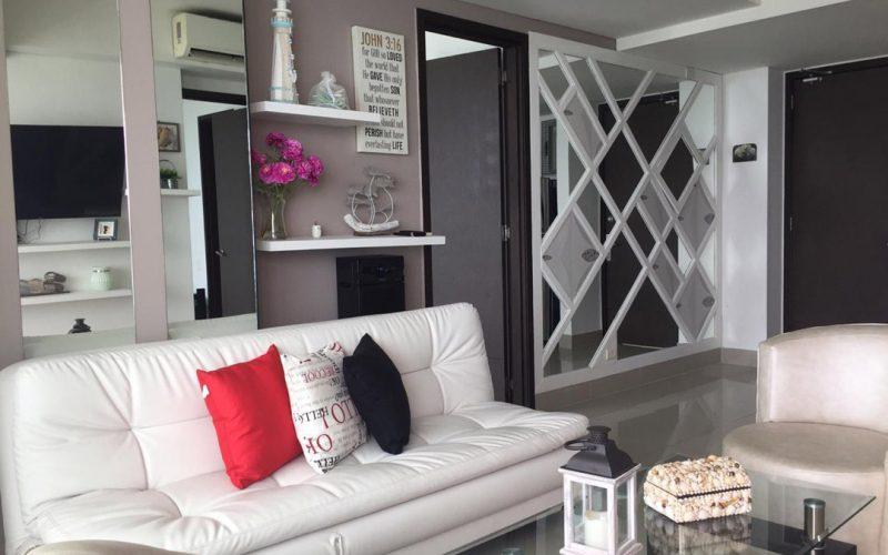 sala de estar de apartamento, con sofá blanco y decoración con tonos rosa y un mural de espejos en forma de diamante