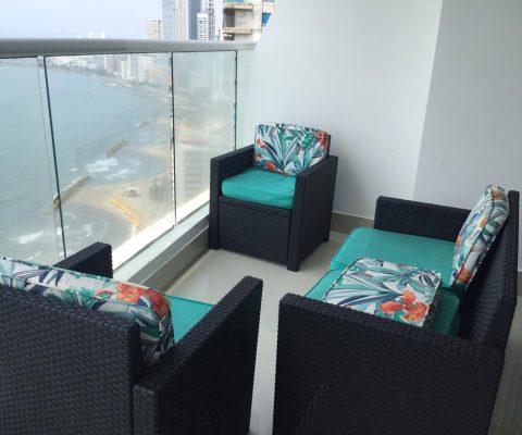 balcón amoblado con sillas coloridas, sofá y 2 poltronas; que ofrece una vista total de la playa de Bocagrande en Cartagena