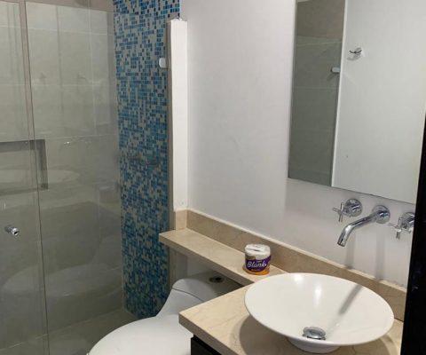 baño con lavamanos de porcelana, grifería moderna, sanitario, encimera de piedra y ducha con detalle de enchape azul