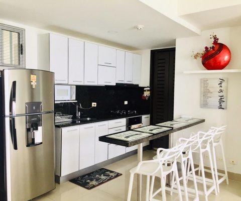 cocina abierta en apartamento, los muebles son blanco y negro con una barra comedor y butacas para 4 personas