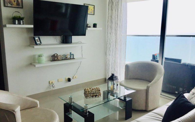 sala de estar en apartamento, 2 sillas, sofá y mesa de café acompañan la decoración moderna, ventanal con vista al mar