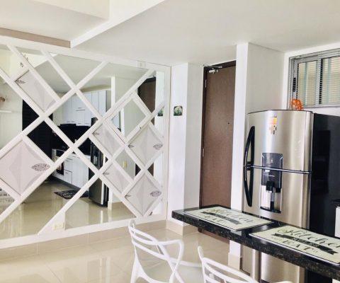 vista parcial de cocina abierta y recibidor de apartamento con decoración mural de espejos en forma de diamante