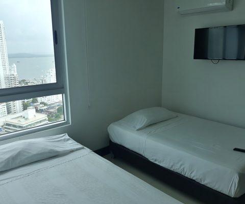 habitación con 2 camas sencillas y tv de pared su ventana amplia da vista sobre la zona de Bocagrande en Cartagena