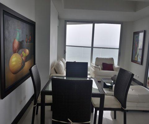 sala comedor de apartamento con muebles en ratán y cuero todos de tonos claros, ventanales dan a un balcón con vista al mar