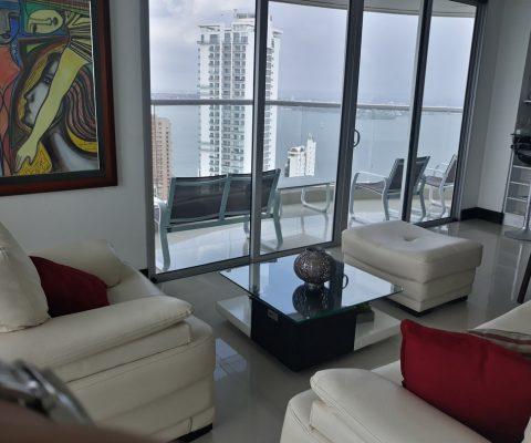 desde una sala de estar se ve el balcón de apartamento que cuenta con 3 sillas y ofrece una vista sobre la bahía de Cartagena