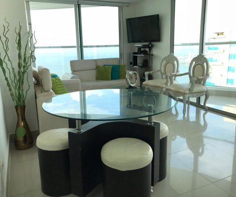 vista general de aparatamento con sala, comedor y balcón, la decoración mezcla lo barroco y moderno en colores claros