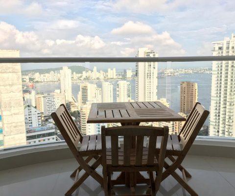 desde un balcón con muebles de madera, mesa y 4 sillas se pueden ver los edificios de Bocagrande y la bahía de Cartagena