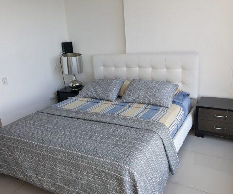 habitación con cama doble y 2 nocheros, los acompaña una lámpara de estilo moderno en tono cromado