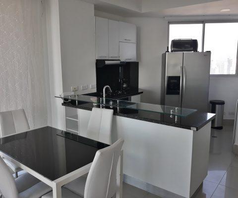 en el comedor de un apartamento está mesa en vidrio con 4 sillas, esto, junto a una cocina abierta de colores blanco y negro