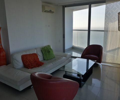 sala de estar en apartamento, amoblada con sofá, 2 poltronas y mesa de café. un ventanal piso techo da vista al mar