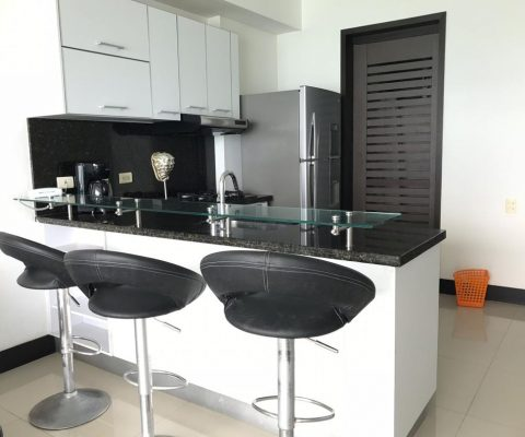 cocina enchapada en colores claros con meson en granito color oscuro con isla de tres puestos incluida