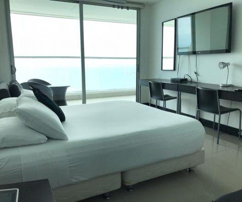 habitacion con cama doble, televisor y escritorio en madera oscura para dos personas con lampara y espejo