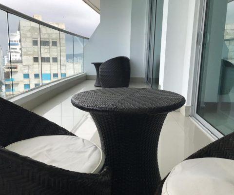 balcon con sala en mimbre color cafe oscuro y almohadas blancas con mesa de centro redonda en mimbre