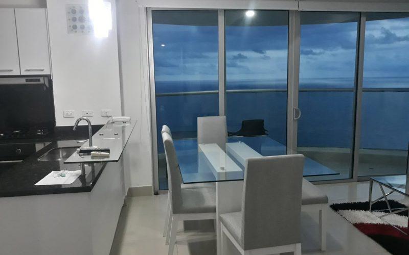 comedor moderno estilo japones de seis puestos bicolor blanco y gris claro cercano al balcon con vista al mar