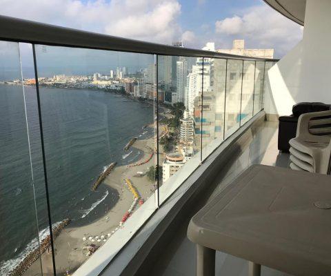 balcon con vista a la playa y mesa rimax color beige de cuatro puestos