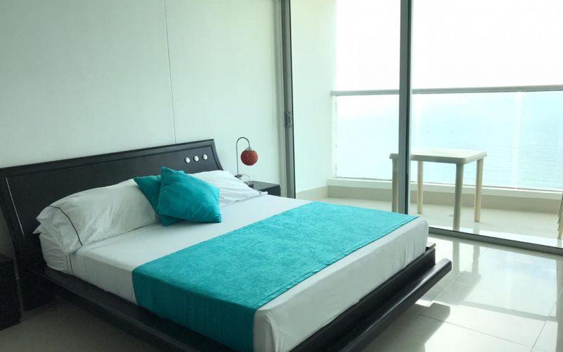 habitacion con cama doble en madera y sabanas blancas y azules, ventanal de piso a techo en vidrio para ingreso al balcon
