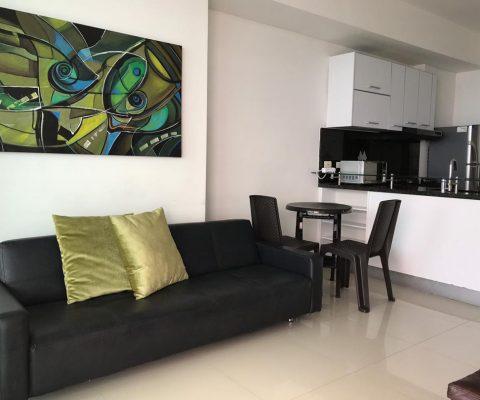 mueble de sala color negro en cuero con un cuadro abstracto en tonalidades verdes