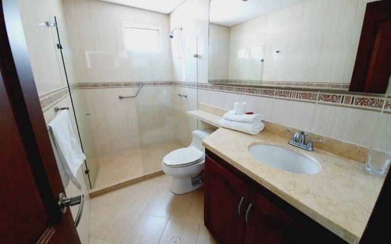 baño enchapado con baldosa beige jaspeada, ducha con division en vidrio