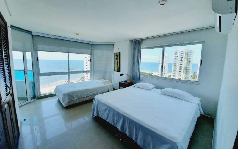 habitacion con cama doble y una cama sencilla, vista al mar de cartagena en colombia