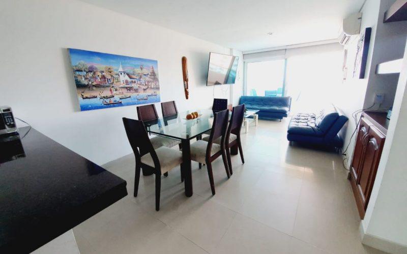 comedor para seis personas, paredes blancas, aire acondicionado, televisor y dos sofas color azul
