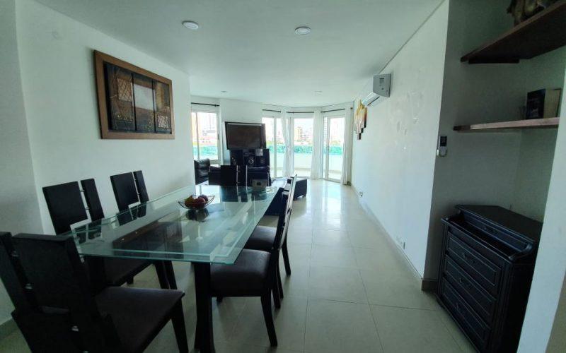 comedor de seis puestos en madera color wengue con mesa en vidrio, piso en ceramica color gris claro y paredes blancas