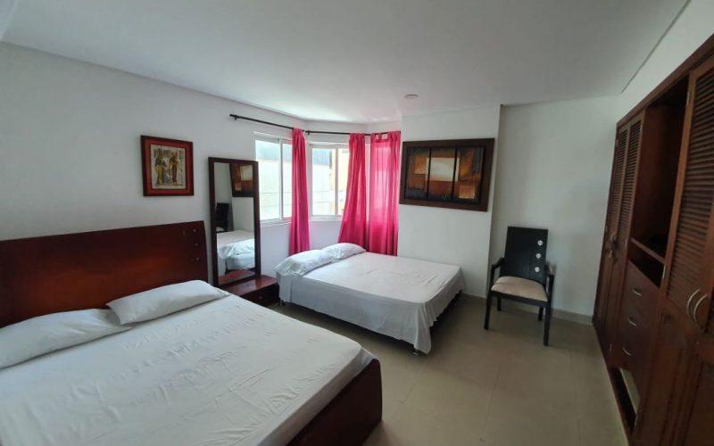 habitacion con dos camas y mesa de noche, closet pared a pared en madera, pisos en ceramica color gris claro