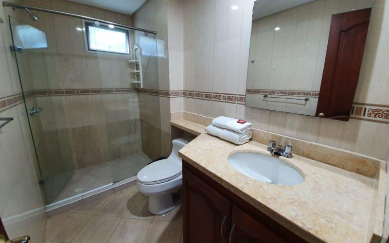 baño con acabados en colores tierra y mueble en madera, division de la bañera en vidrio
