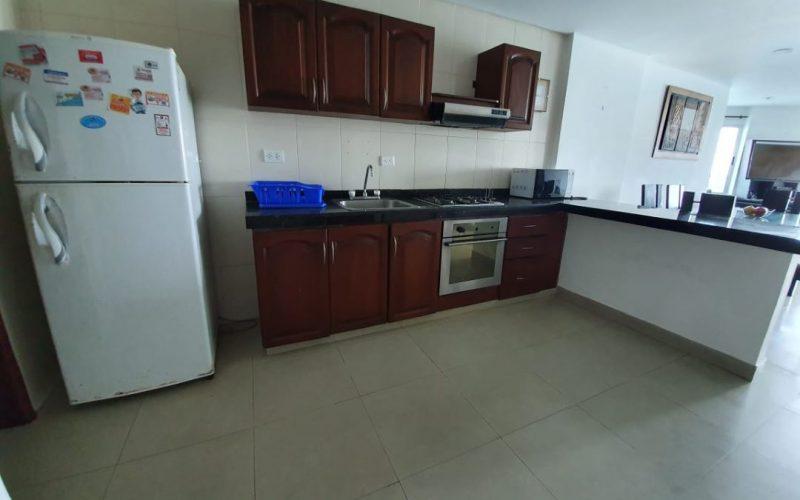 cocina sencilla con gabinetes en madera oscura y meson en granito oscuro, nevera blanca y piso en ceramica color beige