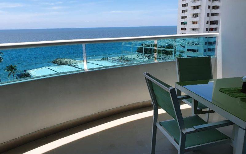 balcon con vista al mar y mesa en madera color blanca y verde